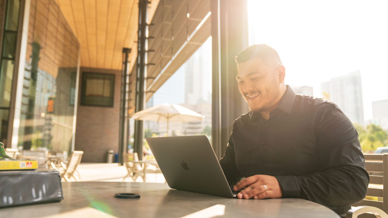 Photograph of a male student sitting at a table with a laptop. He is outside the student center. The sun is low in the sky. The student is smiling.