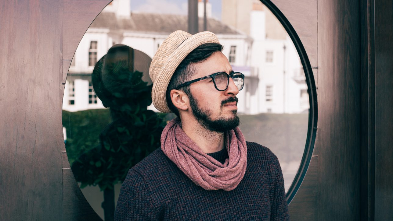 Hip man in hat and scarf in front of round window; photo by Clem Onojeghuo via Unsplash