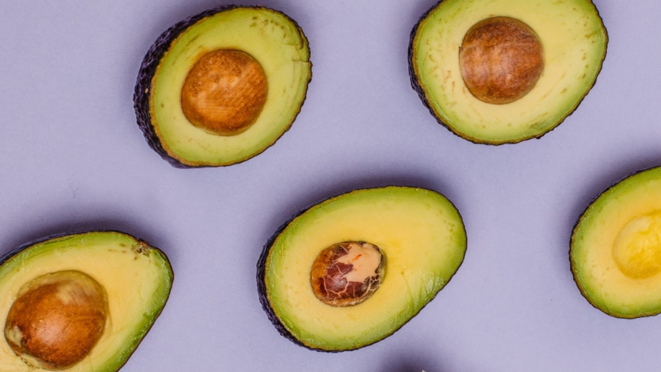 halved avocados on purple background; photo by Curology via Unsplash