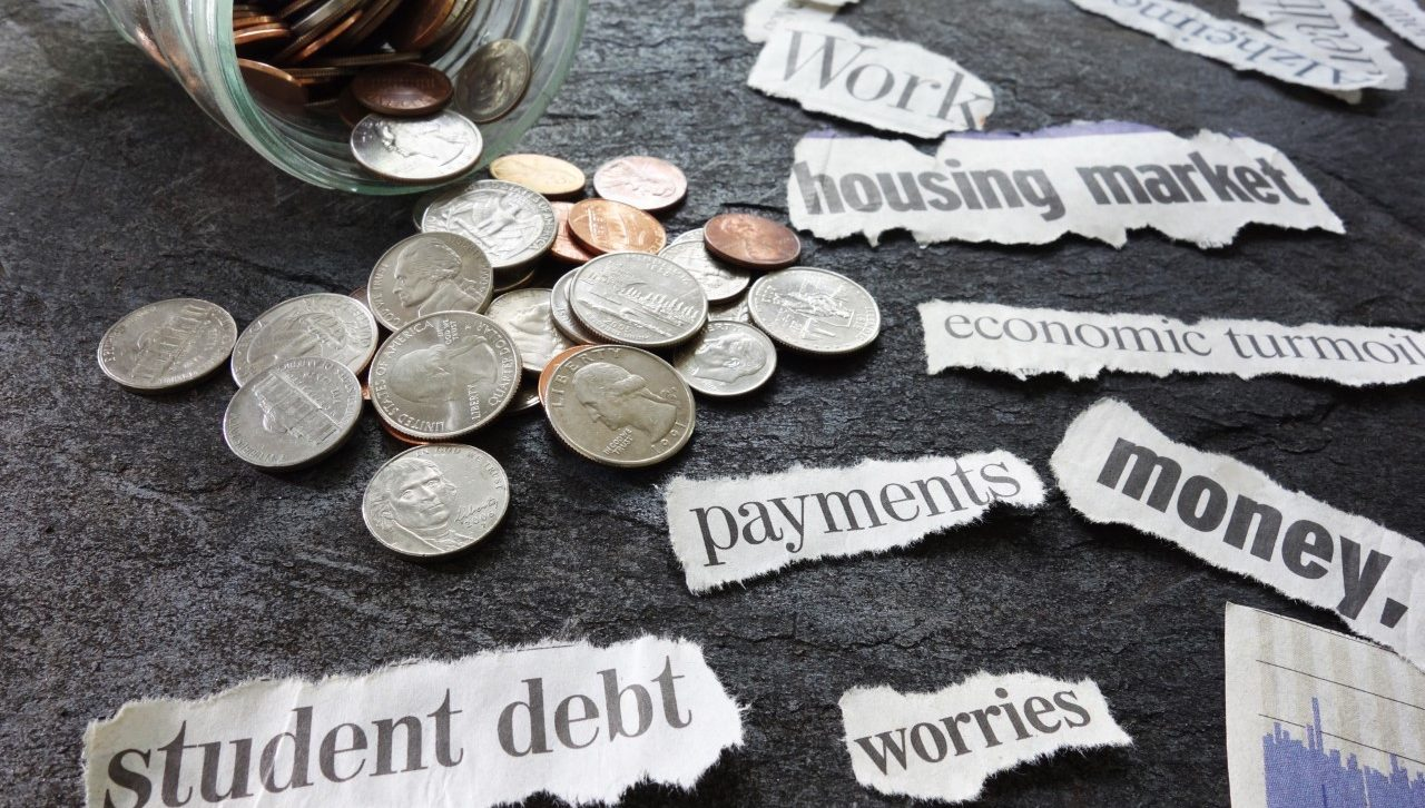 coins on table with signs reading student debt, payments, worries, housing