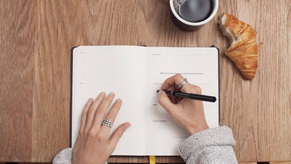 Hands writing in a planner