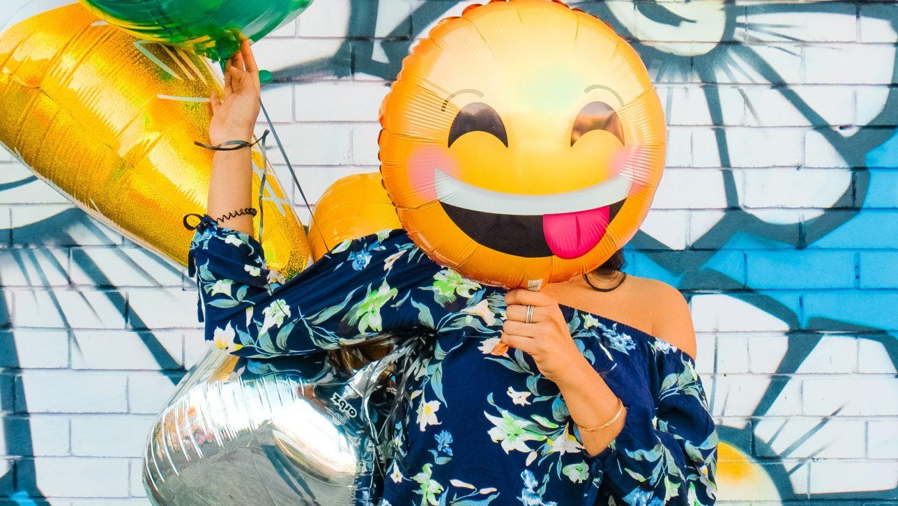 woman holding happy face balloon; photo by Lydia Nada via Unsplash