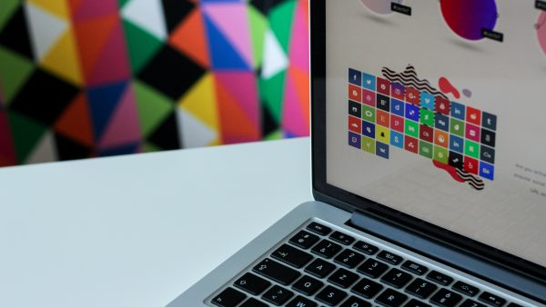 laptop with colorful image on screen; photo by NordWood Themes via Unsplash