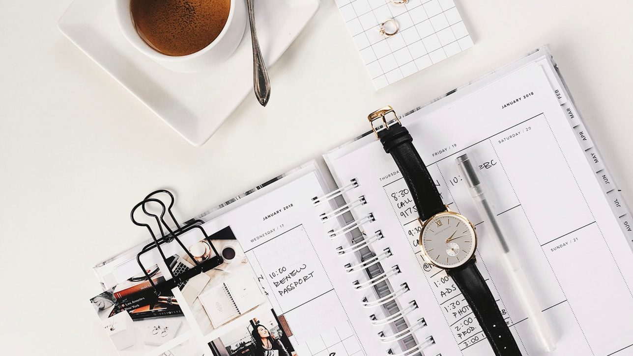 calendar, watch, and cup of coffee on desk; photo by STIL via Unsplash