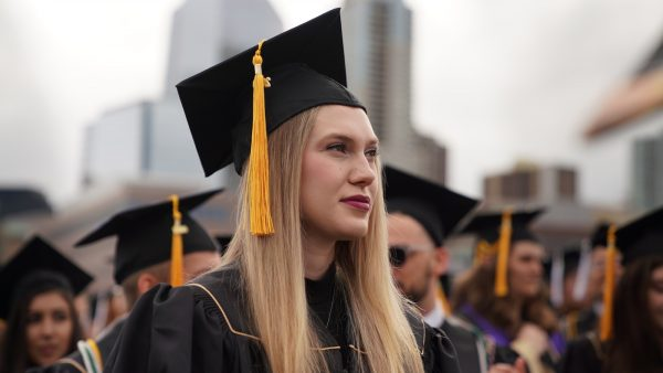 Graduate standing outside at 2019 spring commencement
