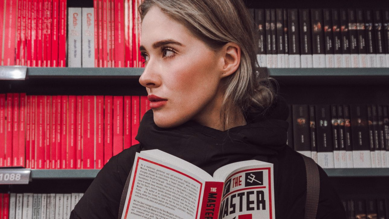 woman in library stacks; photo by Mark Pan4ratte via Unsplash