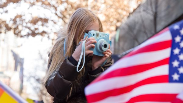woman taking photo os US flag; photo by Mirah Curzer via Unsplash