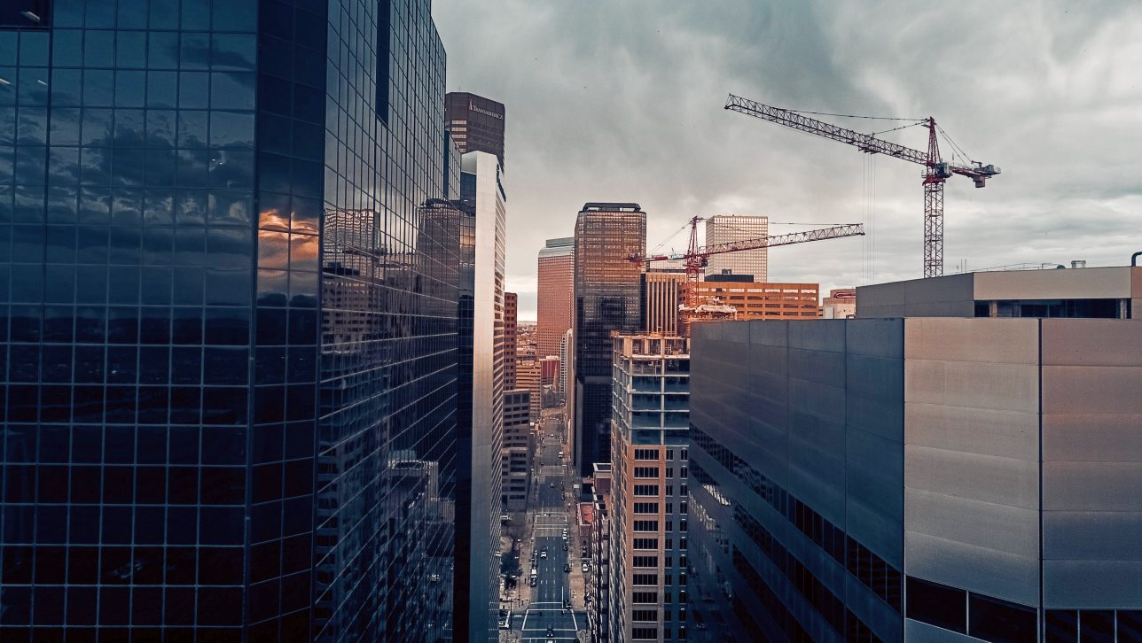 downtown Denver with cranes; photo by Henry desire via unsplash