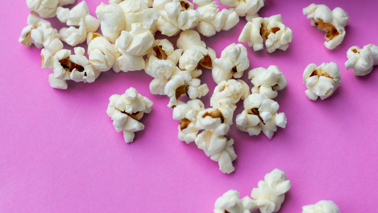popcorn with pink background; photo by Yulia Khlebnikova via Unsplash