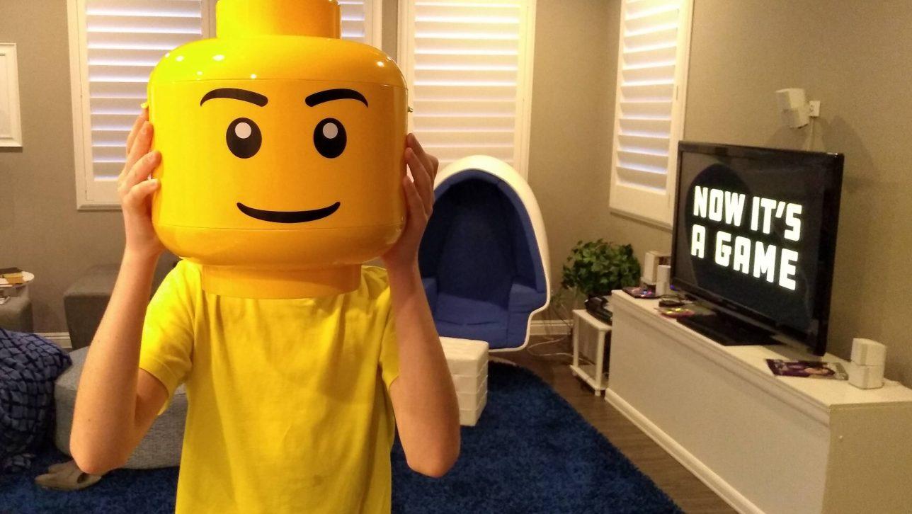 kid holding yellow Lego mask next to TV; photo by David lusvardi via Unsplashh
