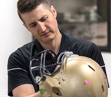 Chris Yakacki, associate professor in College of Engineering, COmputing, and Design inspects football helmet