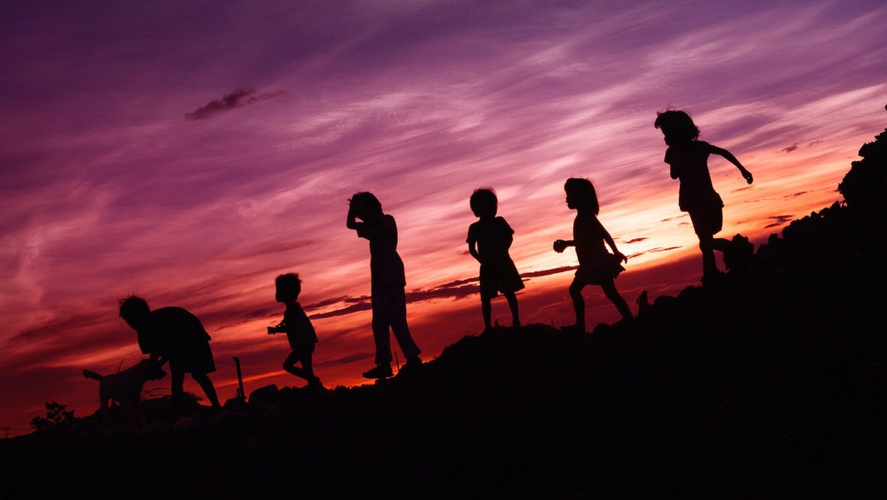 Children walking on a hill with sunset in the back.