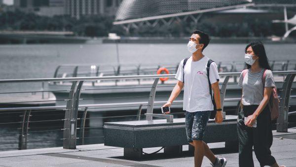 Man and woman walking across bridge wearing masks