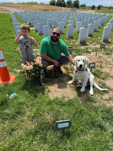Dog with family next to a grave