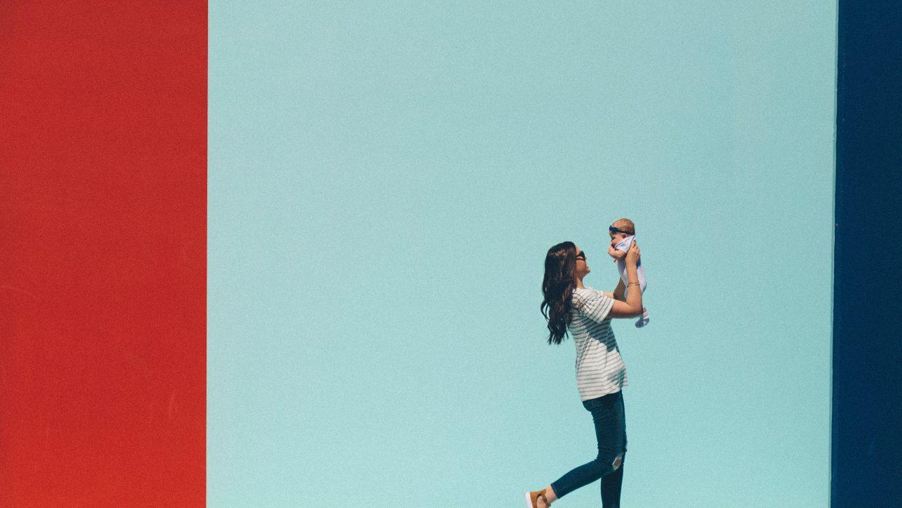 woman holding baby; photo by dakota corbin via unsplash