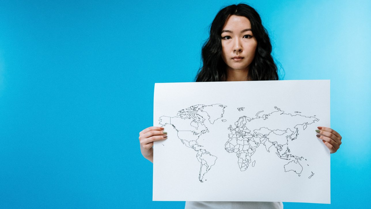 young woman holding map of U.S.; photo by cottonbro via pexels