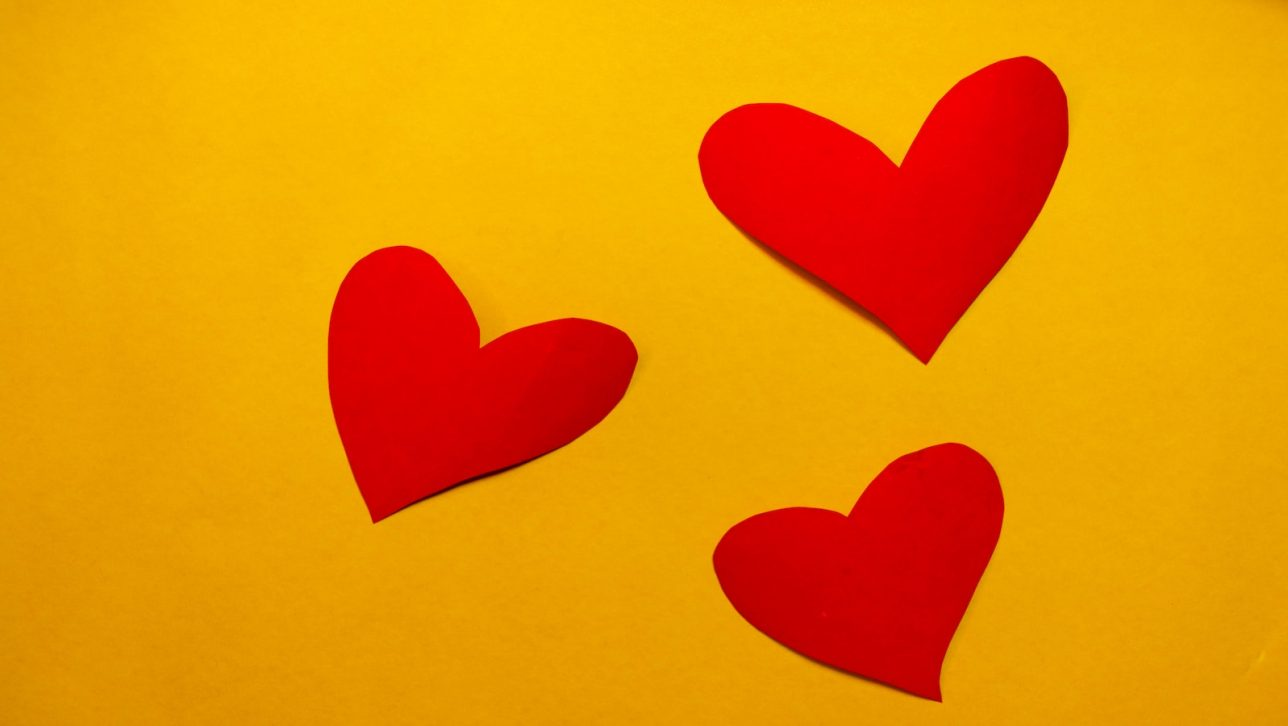 Red paper hearts on a yellow background