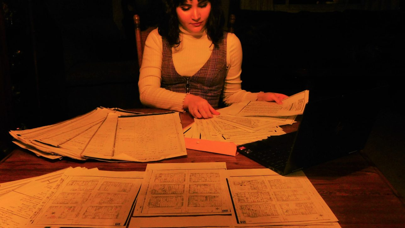 Woman reading a lot of research papers