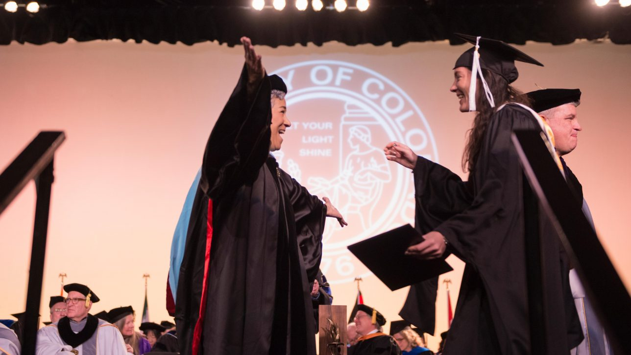 School of Education Dean Emeritus Rebecca Kantor greeting her daughter on a graduation stage