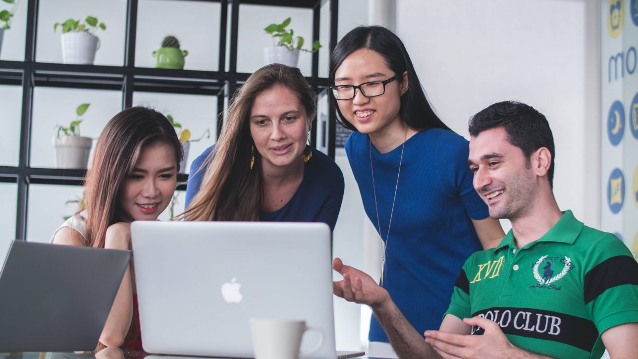 Four college students standing in front of a laptop smiling