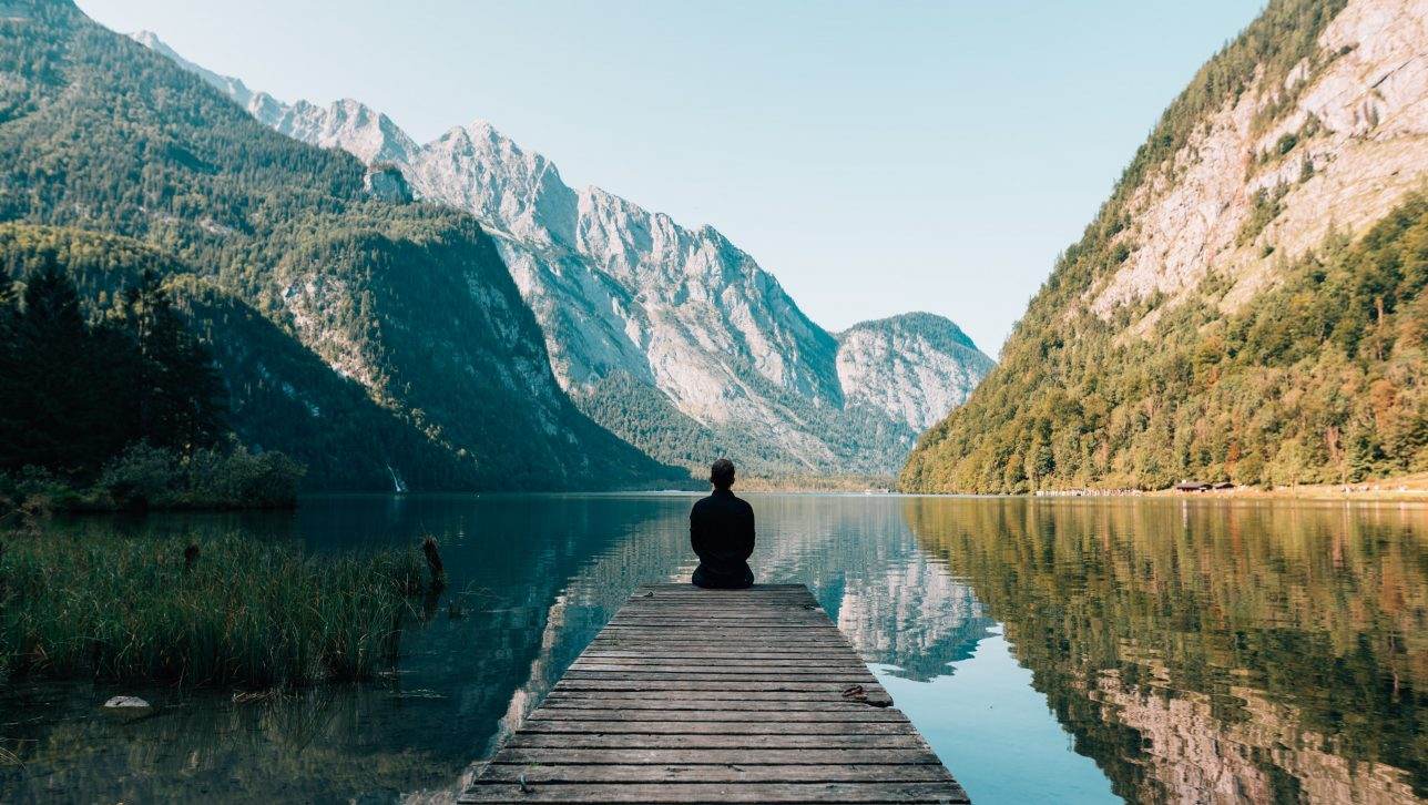 Person sitting on end of deck and looking at landscape scenery