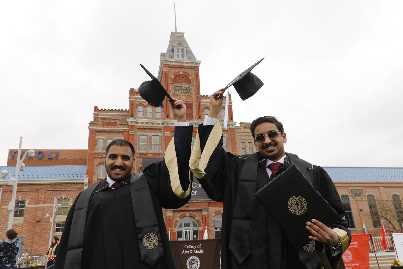 Graduates holding graduation caps