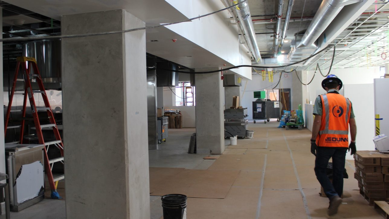 Project manager walking through dining hall currently in construction