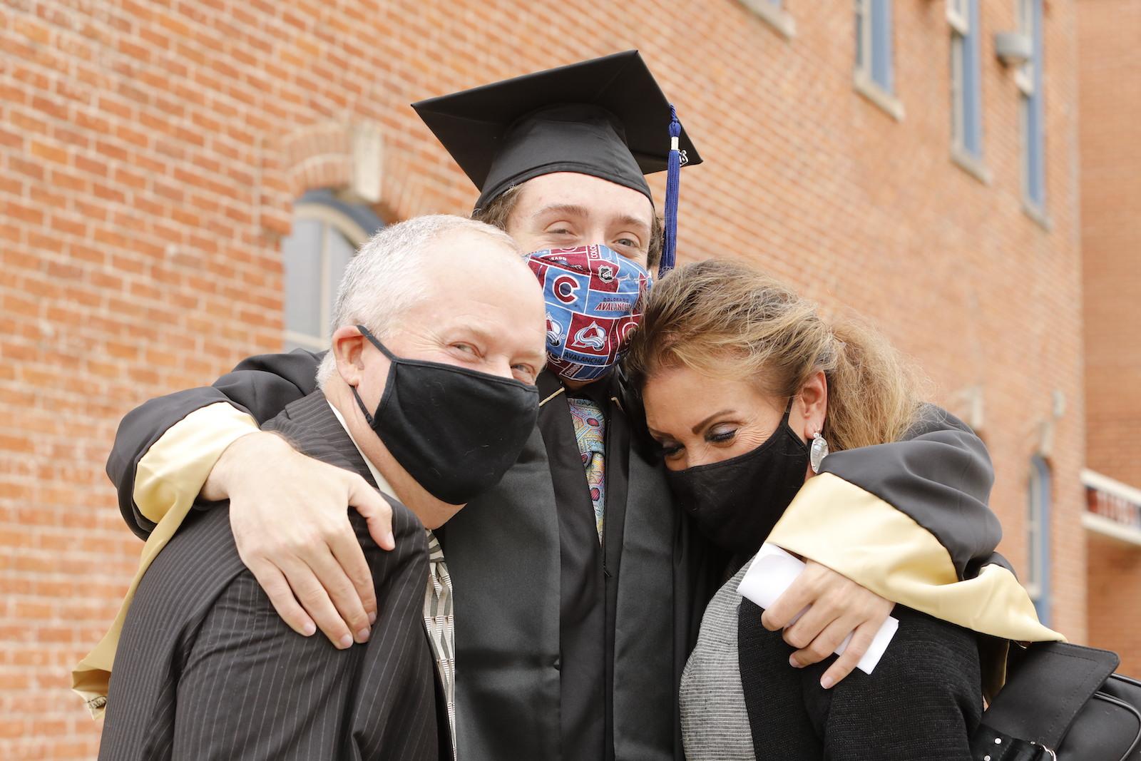 Graduate hugging family