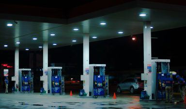 Cars driving by gas station during evening