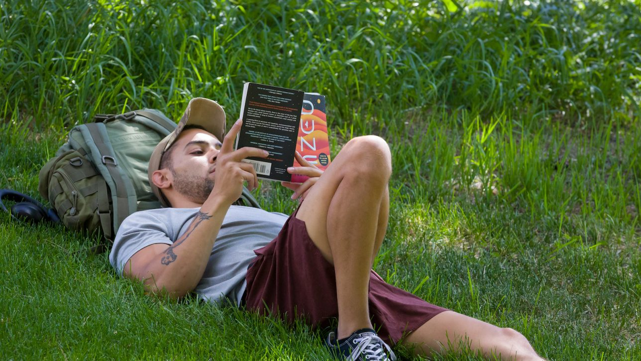 Student reading a book on grassy field