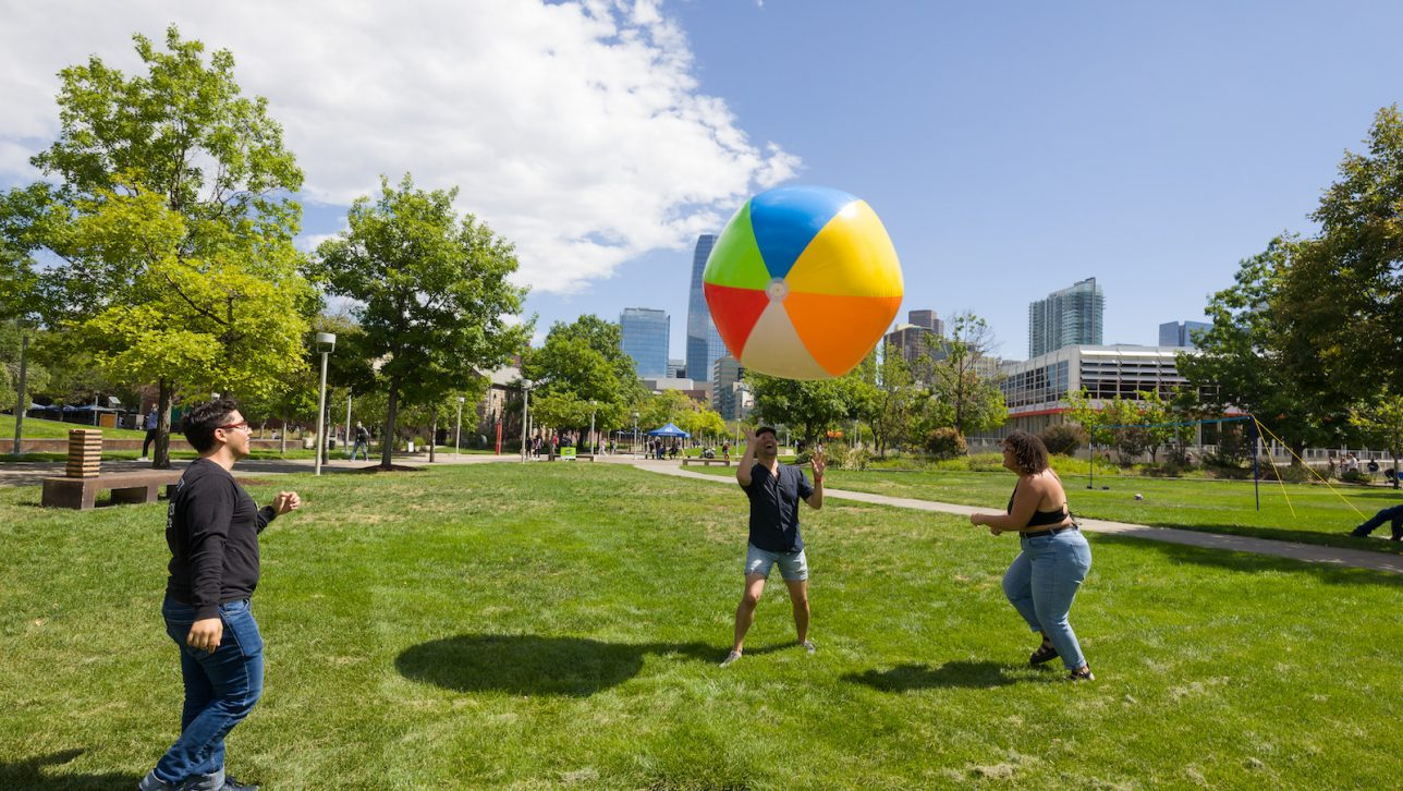 Students playing with beach ball on grassy field