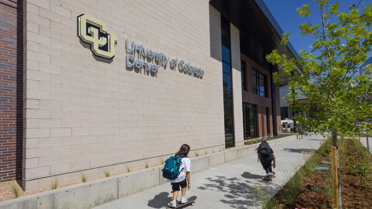 Students skateboarding by CU-Denver building
