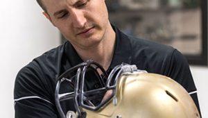 Chris Yakacki, associate professor in College of Engineering, COmputing, and Design inspects football helmet